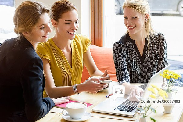 Three young women looking at laptop in cafe