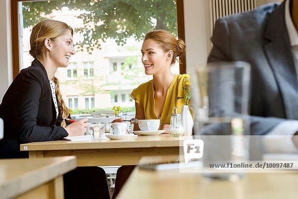 Zwei junge Freundinnen beim Plaudern im Cafe