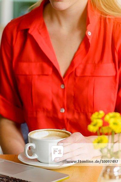 Cropped Nahaufnahme der jungen Frau im Café trinken Kaffee  während mit dem Laptop