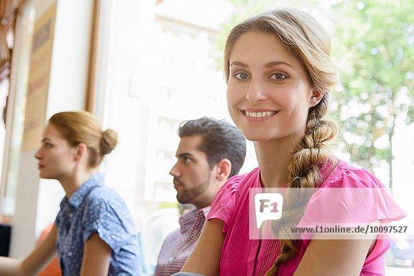 Porträt einer jungen Frau im Café mit Freunden