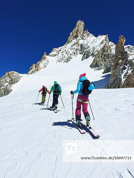 Rückansicht von drei erwachsenen Skifahrern  die das Mont-Blanc-Massiv erklimmen  Graian Alps  Frankreich