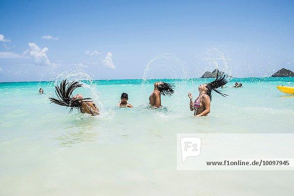 Side view of young women throwing long wet hair back in sea at Lanikai Beach  Oahu  Hawaii  USA