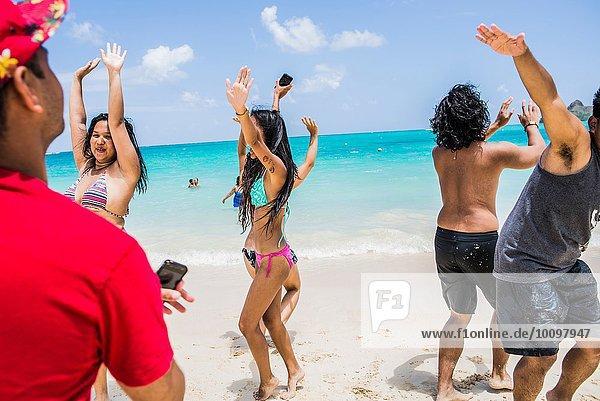 Junge erwachsene Freunde tanzen am Lanikai Beach  Oahu  Hawaii  USA