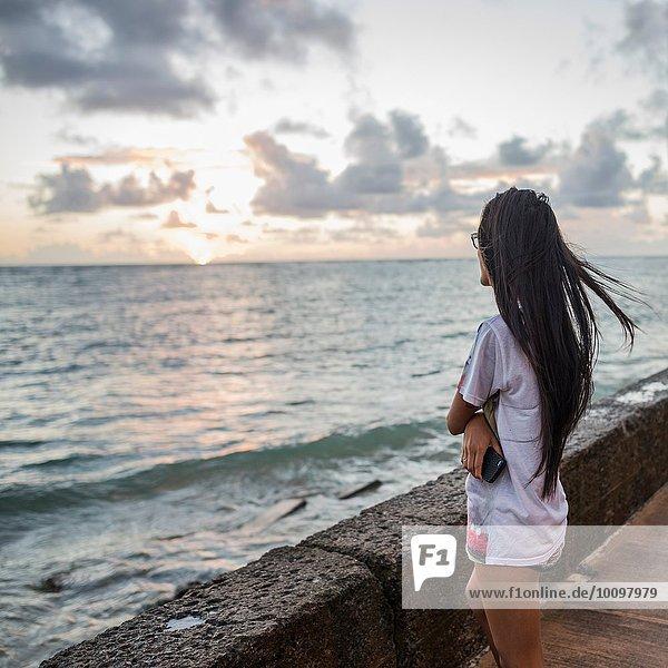 Junge Frau beim Sonnenaufgang  Kaaawa Strand  Oahu  Hawaii  USA