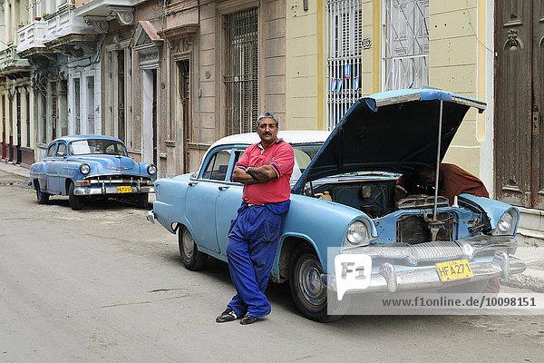 Mann neben amerikanischem Oldtimer  der auf der Straße repariert wird  Centro Habana  Havanna  Ciudad de La Habana  Kuba  Nordamerika