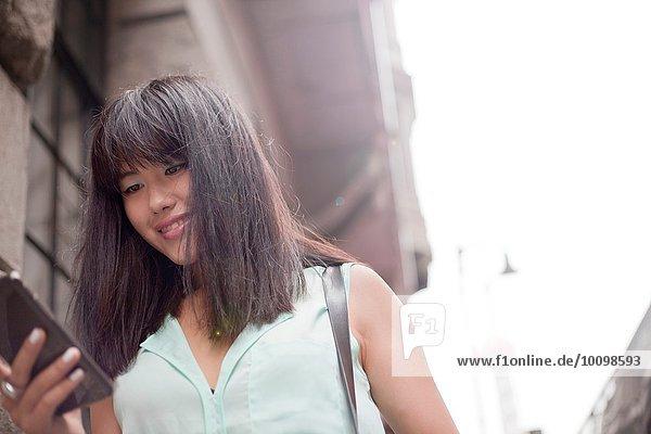 Junge Geschäftsfrau  mit Smartphone  im Freien  Shanghai  China