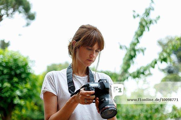 Mittlere erwachsene Frau mit Blick auf die Digitalkamera