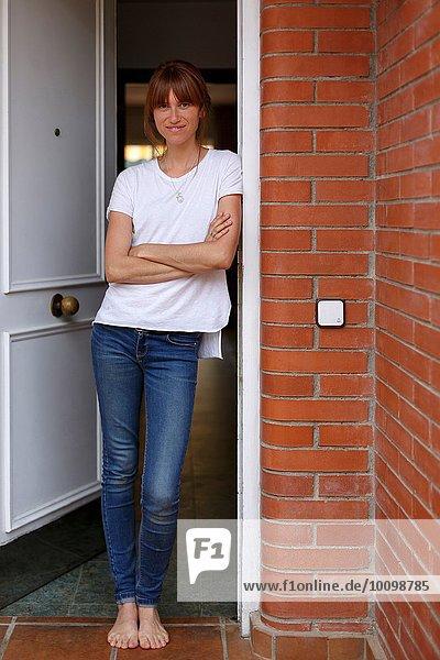 Gesamtansicht der mittleren erwachsenen Frau  die sich gegen den Türrahmen lehnt  die Arme gekreuzt.