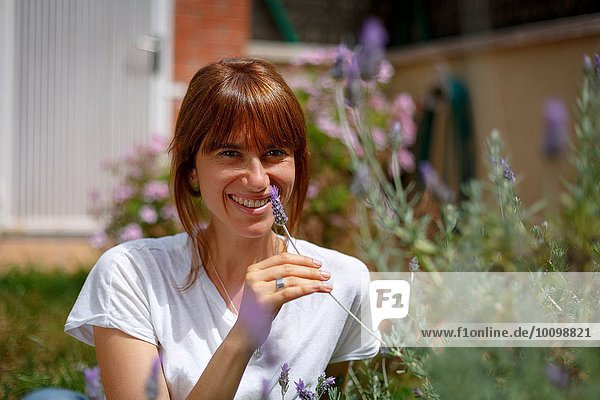 Mid adult woman sitting smelling lavender  smiling at camera