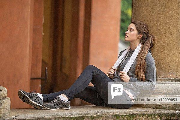 Junge Frau in Sportbekleidung sitzend ruhend