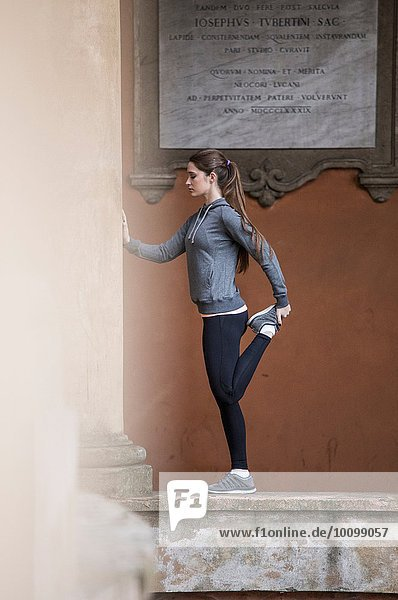 Junge Frau in Sportbekleidung mit gestrecktem Bein