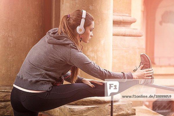 Junge Frau in Sportbekleidung und Kopfhörer  die die Beine strecken