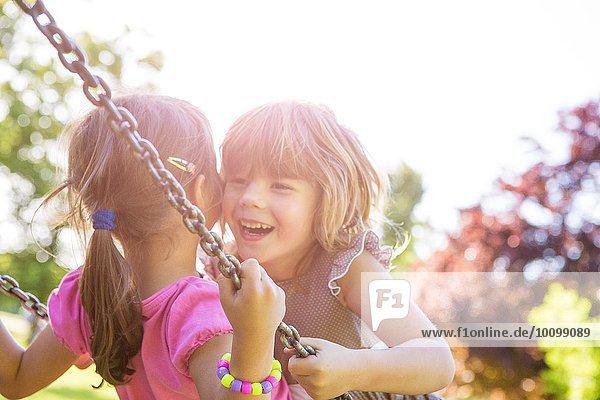 Zwei junge Mädchen  die von Angesicht zu Angesicht auf der Parkschaukel schwingen.