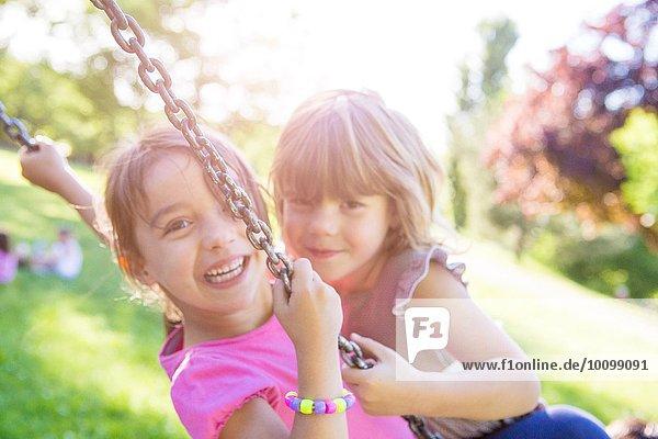 Porträt von zwei jungen Mädchen  die zusammen auf einer Parkschaukel schwingen.