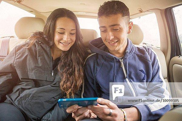 Teenager Mädchen und junger Mann lesen Smartphone-Text im Auto Rücksitz