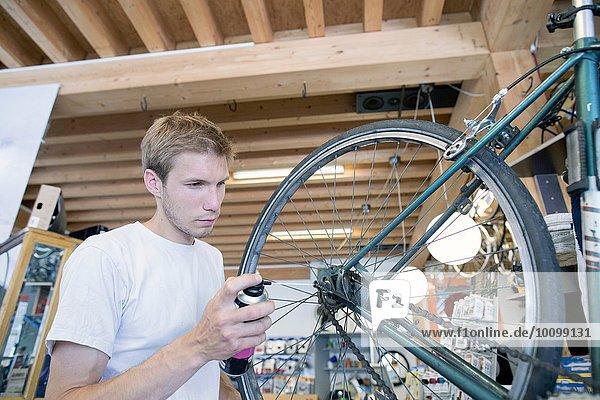 Mittlerer Erwachsener Mann in der Werkstatt  der das Fahrrad schmiert.