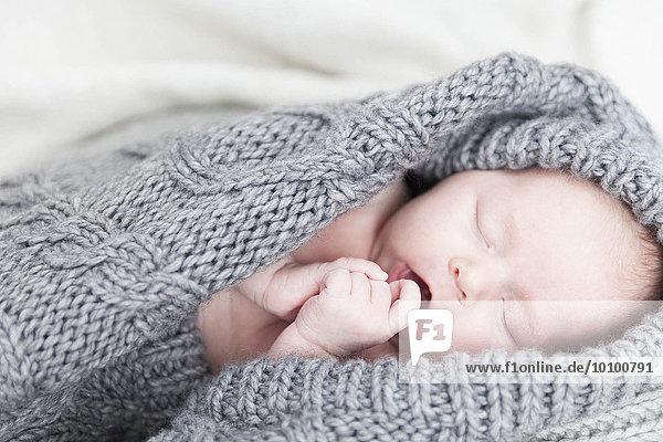 Weibliches Baby in grauer Strickjacke Weibliches Baby in grauer Strickjacke