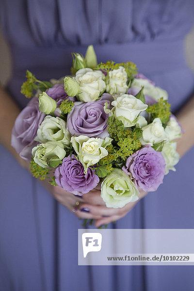 Eine Brautjungfer in einem blauen Kleid  die einen Strauß rosa und weißer Rosen hält.