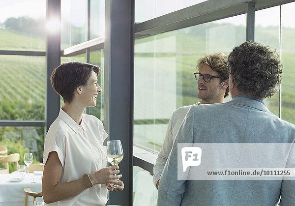 Freunde trinken Weißwein im Verkostungsraum des Weingutes