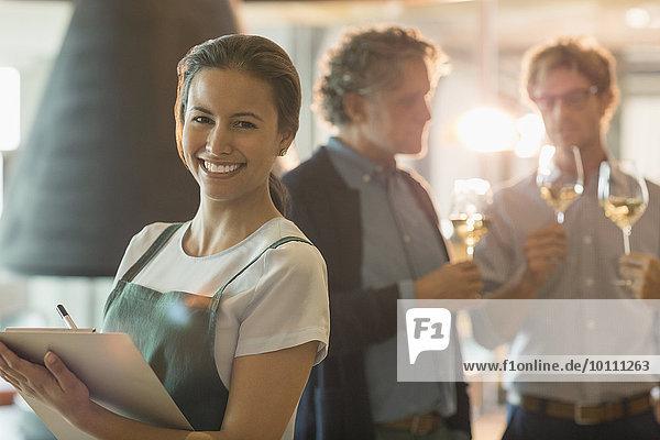 Portrait lächelnde Frau mit Zwischenablage im Weinverkostungsraum