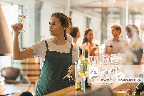 Weinverkostungsraummitarbeiter bei der Untersuchung von Weißwein