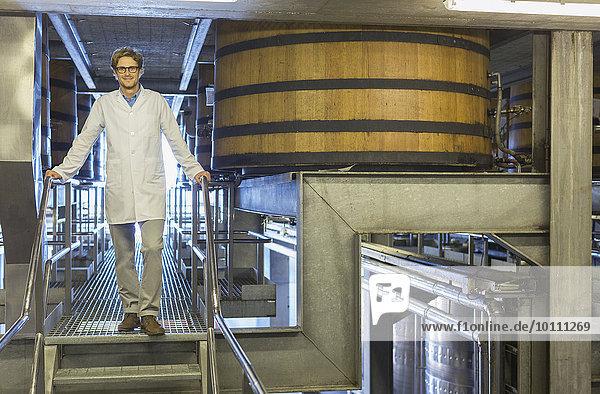 Portrait selbstbewusster Winzer im Laborkittel auf Plattform im Weinkeller