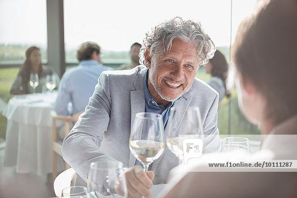 Lächelndes Paar trinkt Wein im sonnigen Restaurant