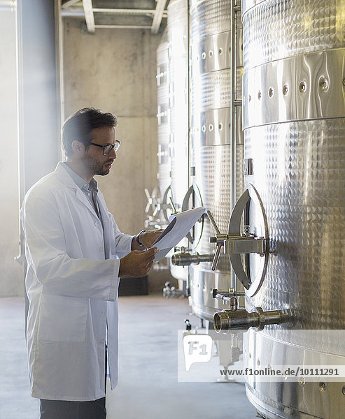 Winzer im Laborkittel mit Klemmbrett und Edelstahlbehälter im Weinkeller