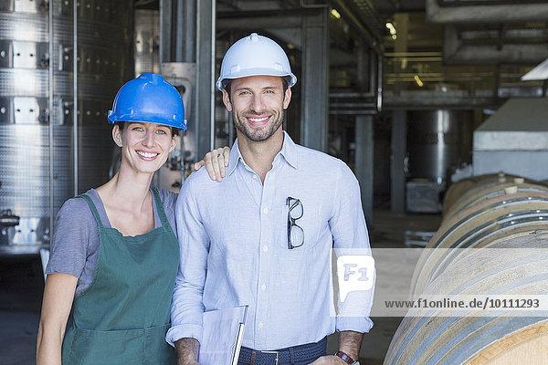 Portrait selbstbewusste Weinkellerei-Mitarbeiter mit Schutzhelmen im Keller