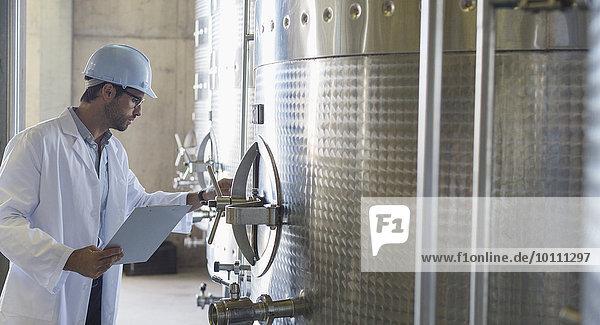 Winzer in Laborkittel und Schutzhelm bei der Untersuchung von Edelstahlbehältern im Keller