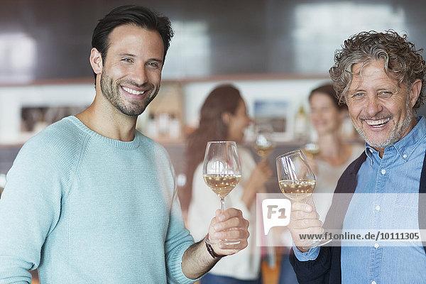 Portrait lächelnde Männer Weinverkostung im Weinkeller