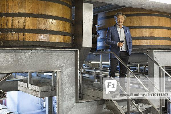 Portrait selbstbewusster Winzer mit Rotwein auf Plattform im Weinkeller