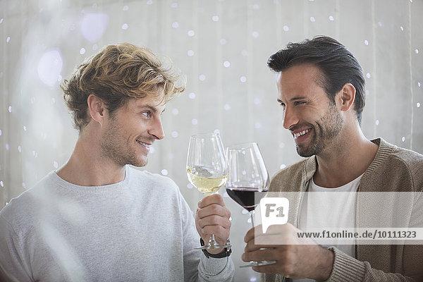 Lächelnde Männer stoßen auf Weingläser an
