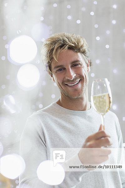 Portrait lächelnder Mann trinkt Weißwein