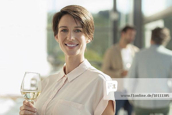 Portrait lächelnde Frau trinkt Weißwein