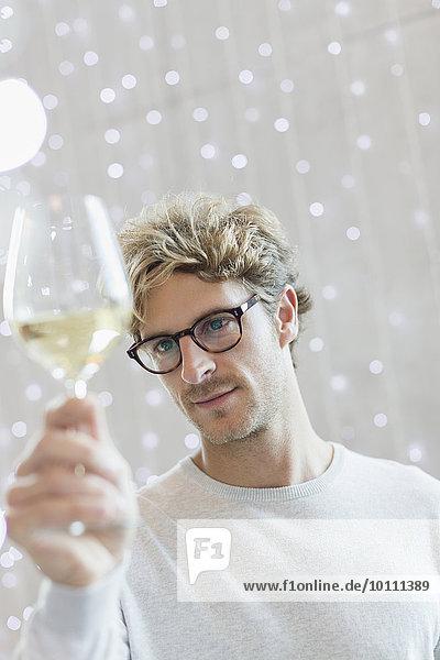 Close-up-Mann bei der Untersuchung von Weißwein