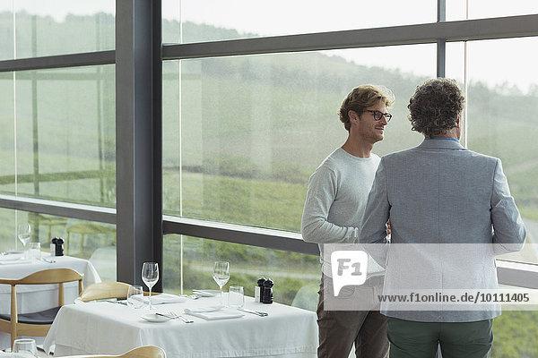 Männer beim Essen im Weinkellerfenster