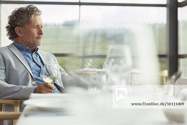 Nachdenklicher Mann trinkt Weißwein im Speisesaal des Weingutes