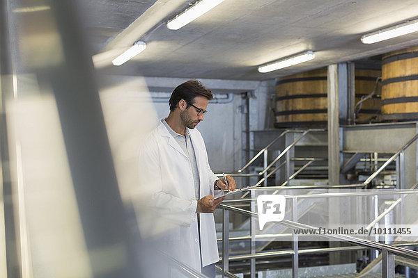 Winzer im Laborkittel mit Klemmbrett im Weinkeller