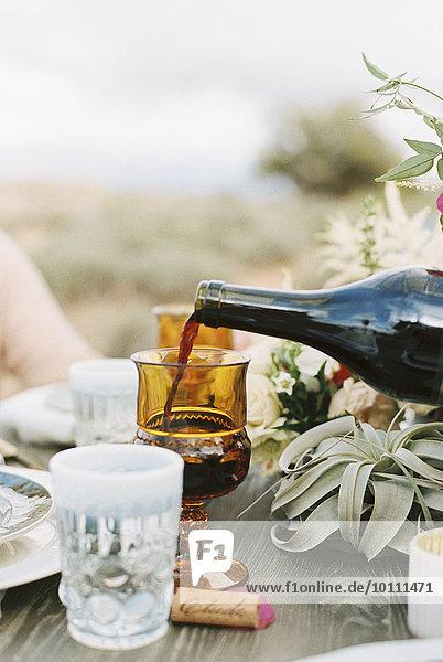 Glas eingießen einschenken über Rotwein Ansicht Außenaufnahme Tisch