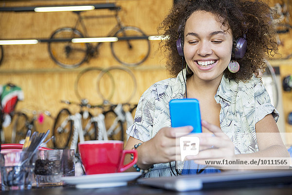 Smiling woman with headphones texting on cell phone in bike shop