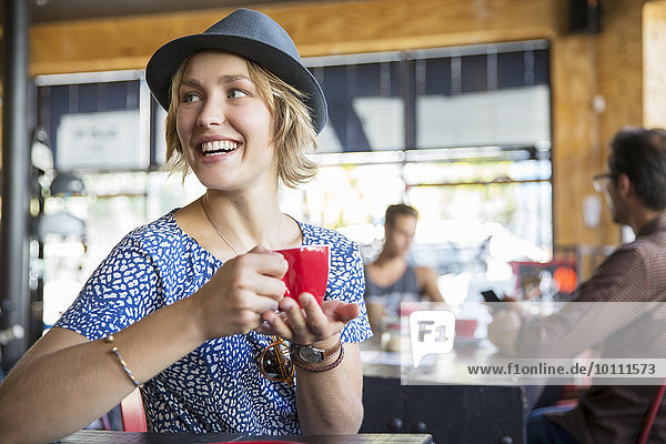 Smiling woman drinking coffee looking over shoulder in cafe