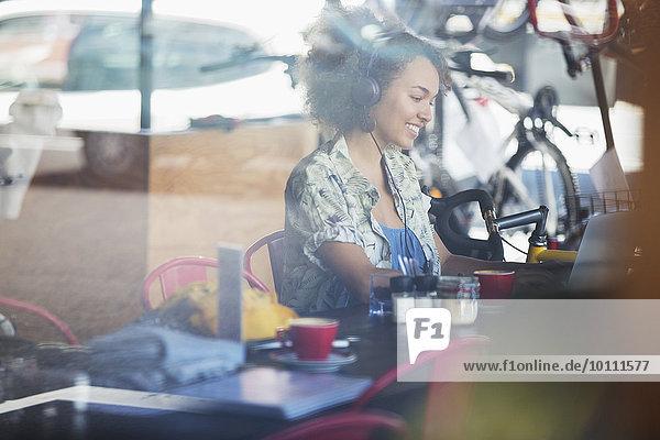 Lächelnde Frau mit Kopfhörer am Laptop im Cafe