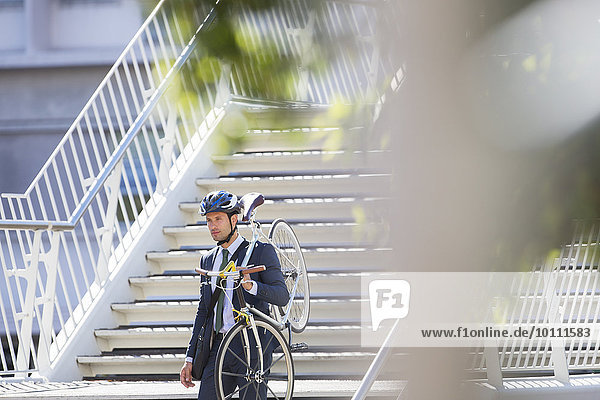 Businessman in suit and helmet carrying bicycle down urban stairs