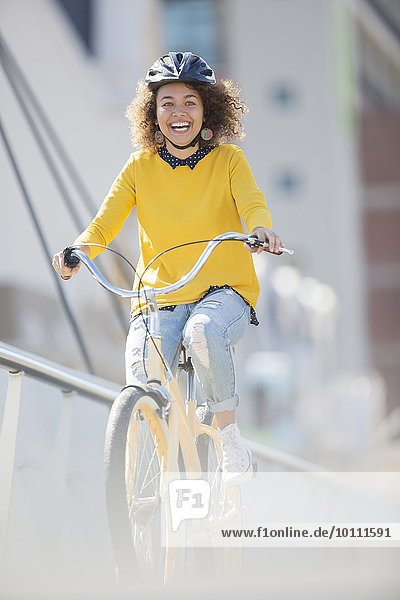 Enthusiastic woman in helmet riding bicycle