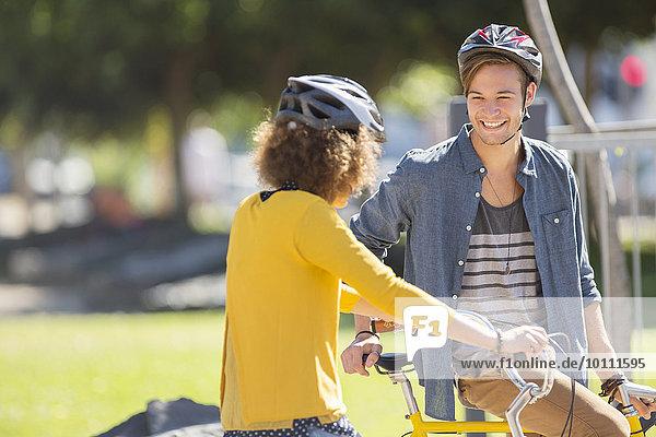 Mann und Frau mit Fahrrädern  die Helme tragen und sich im Park unterhalten.