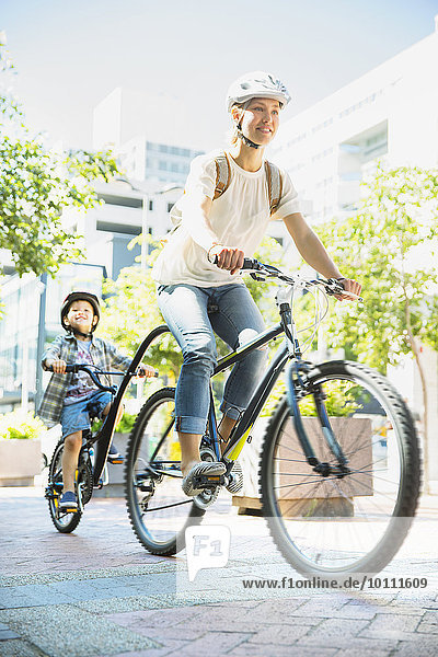 Mother and son riding bicycles on urban path