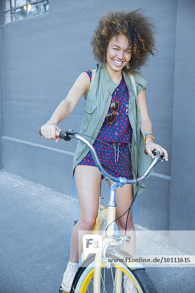 Portrait lächelnde Frau mit Afro auf Fahrrad
