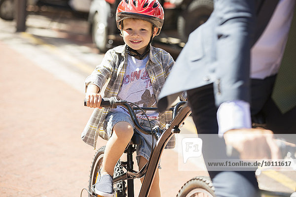 Portrait smiling boy riding bicycle on sunny road