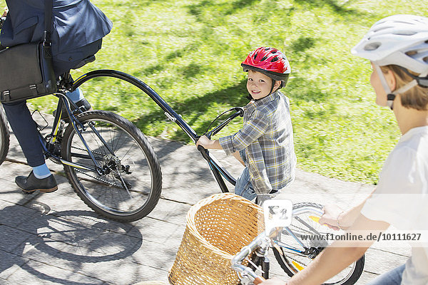 Portrait smiling boy riding tandem bicycle with father in park